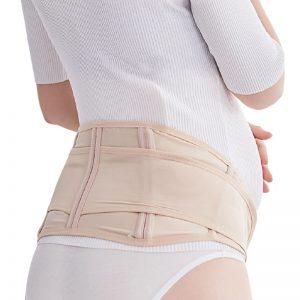 Femme de dos portant la ceinture d'ajustement grossesse de couleur beige