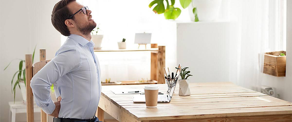 Homme devant son ordinateur souffrant de douleurs lombaires
