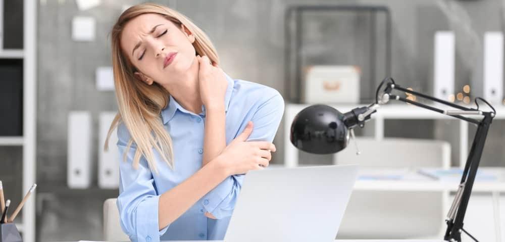 Femme au bureau avec des douleurs au cou