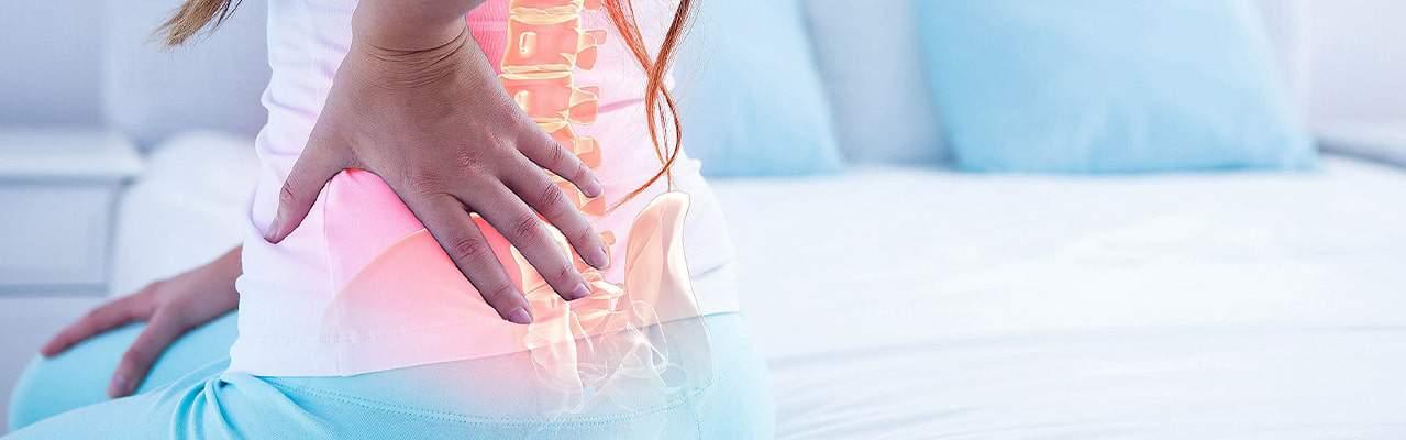 Femme sur son lit avec des douleurs lombaires