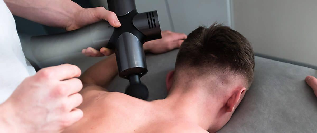 Homme profitant d'une relaxation profonde avec un pistolet de massage