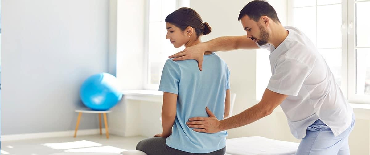 Ostéopathe examinant une jeune femme ayant mal au dos dans un hôpital moderne