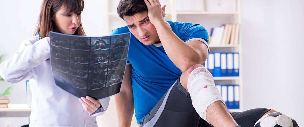 Jeune homme chez le médecin suite à une blessure au genou lors d'une partie de football