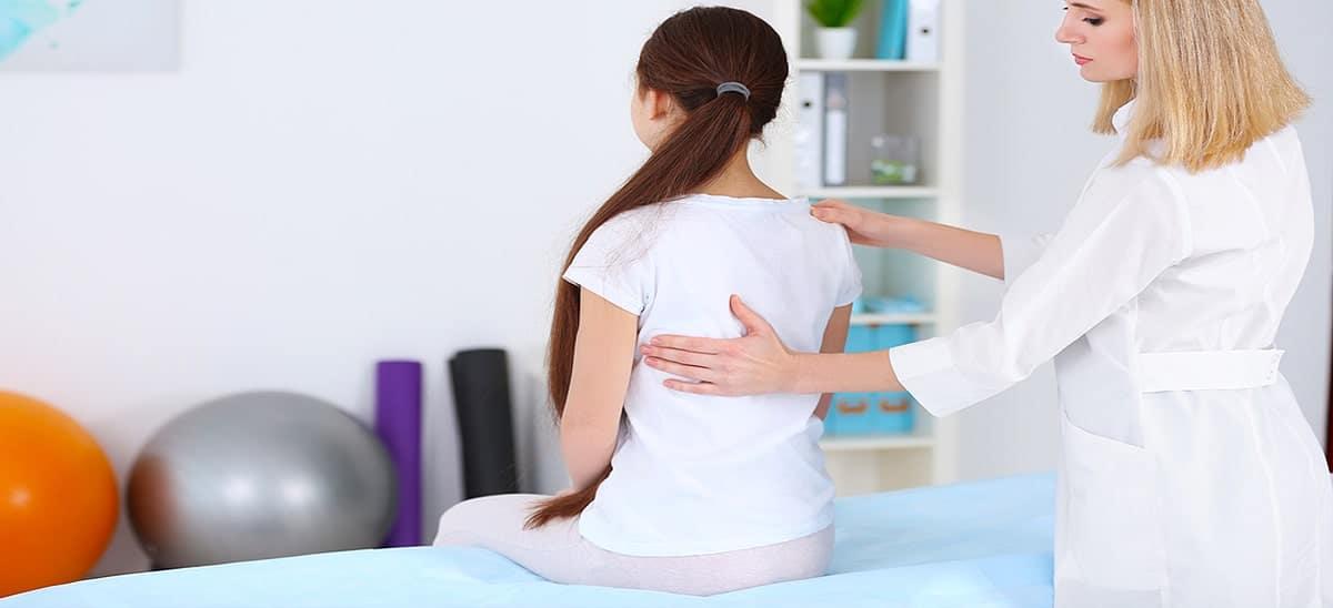 Enfant chez un kinésithérapeute pour des douleurs au dos à cause d'une mauvaise posture