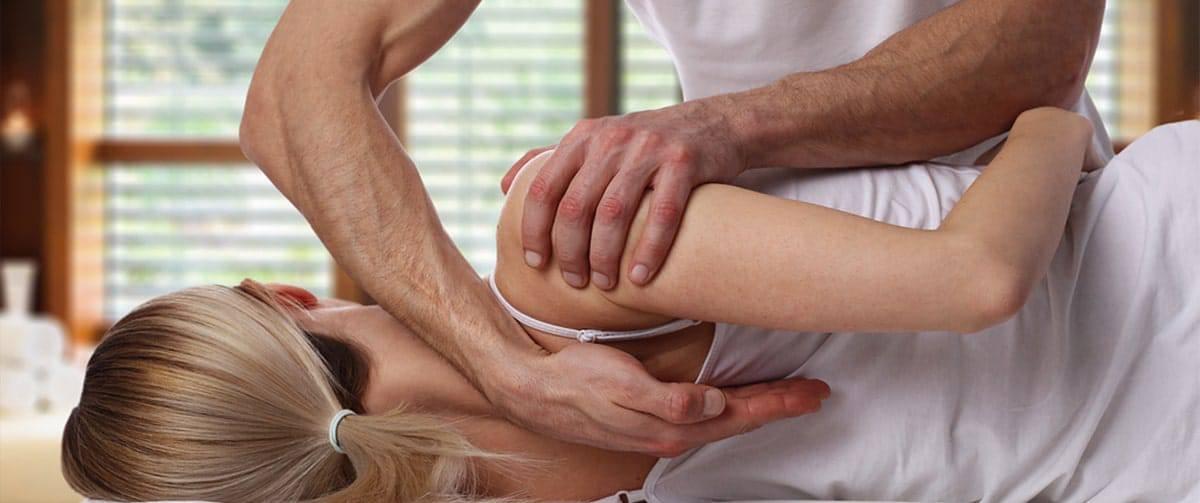 Kinésithérapeute débloquant l'articulation de l'épaule d'une patiente