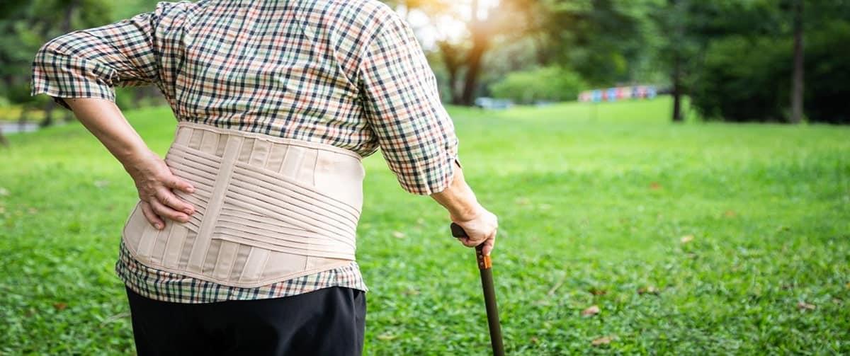 Personne âgée souffrant de douleurs au dos et portant une ceinture lombaire