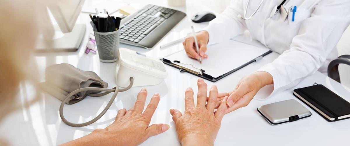 Femme chez le médecin souffrant d'arthrite aux mains
