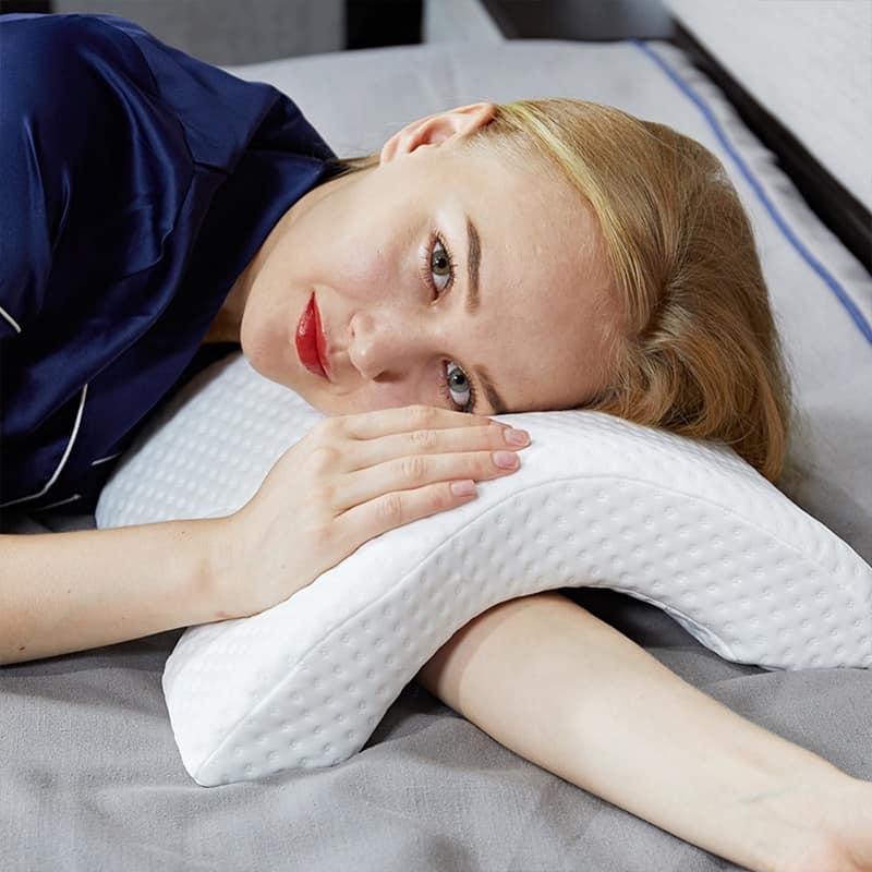 Femme dans son lit avec son oreiller ergonomique cervical avec mousse à mémoire de forme